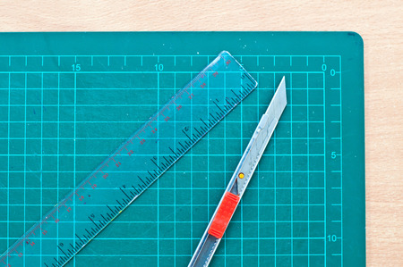 wood cutter: cutter and ruller and green cutting mat on wood table Stock Photo