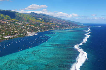 Taking off from Papeete airport. Astonishing beauty of the barrier reef surrounding Tahiti island.