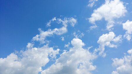 pleasent: bright blue sky with puffy white clouds.