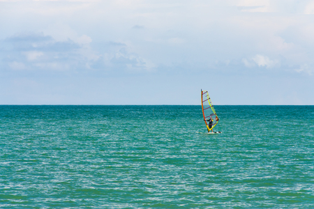 wind surfing: Calm wind surfing with the sun and wind as the driving force on this day.