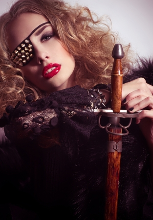 Beautiful girl with bandage on an eye and  sword  Fashion portrait of pirate photo