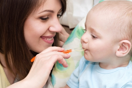 Young mother feeding baby boy