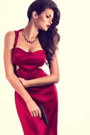 high fashion: Beautiful young woman with revolver in red dress