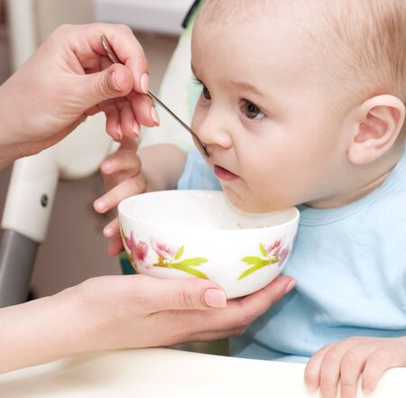 baby eating: Mother s hand feeding baby boy