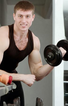 体育館でハンサムな若い筋肉スポーツ男