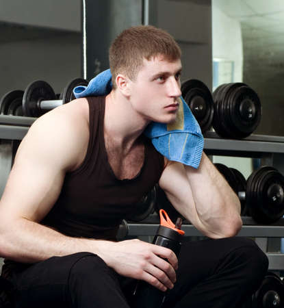 Handsome young muscular sports man in gymnasium photo