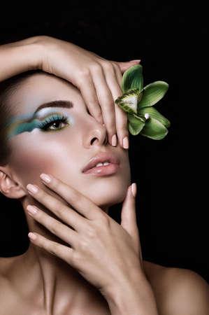メイクや花の美しい若い女性の肖像画