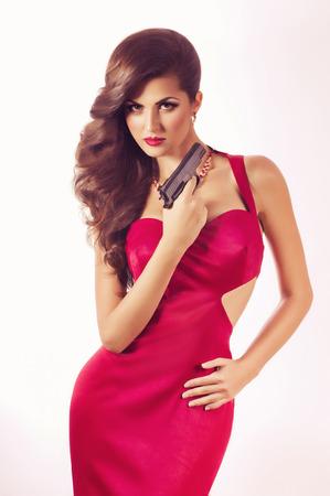 赤いドレスのリボルバーと美しい若い女性