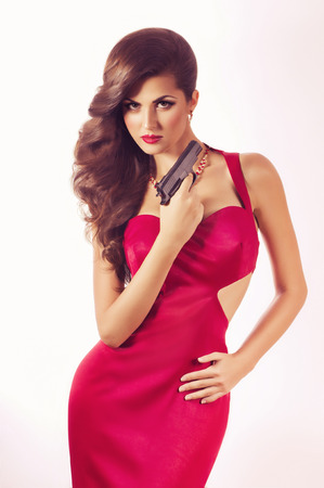 Beautiful young woman with revolver in red dress