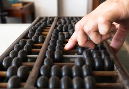 abaci: Womans hands accounting with the old abacus