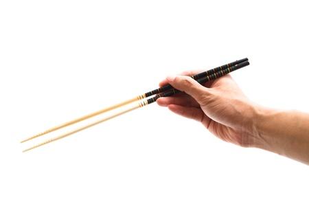 Hand holding chopsticks, isolated on white background.