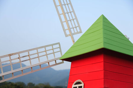 colored wooden house with windmill in park Stock Photo