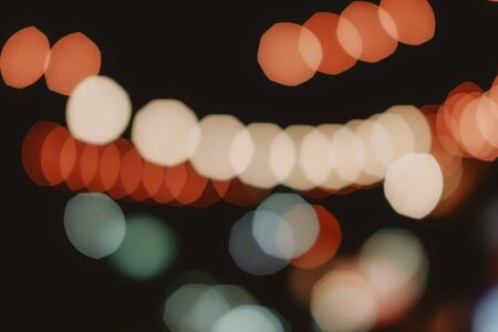 Orange, blue and white bokeh light. Abstract or blurred of light glitter. Glow texture background. Moody tone.