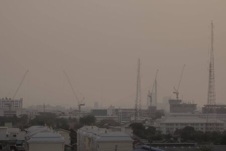 Air pollution from Lots of dust or PM2.5 particle exceeds the standard (AQI) at Bangkok, Thailand. Negative effect on Respiratory system and health. The construction with tower crane.