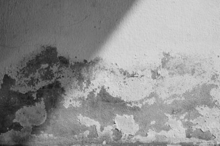 Close-up of White cement crack wall and peeled paint caused by water and sunlight. Peel wall of White house paint with black stain. Black and White of Texture background. Stock Photo