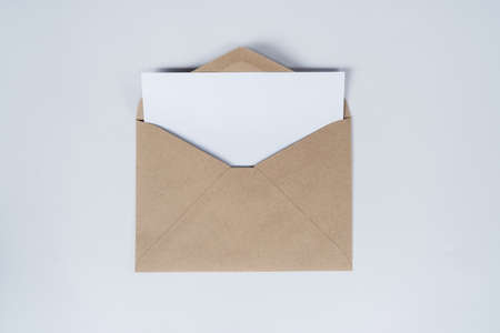 Blank white paper is placed on the open brown paper envelope. Mock-up of horizontal blank greeting card. Top view of Craft paper envelope on white background. Flat lay of stationery. Minimalism style.