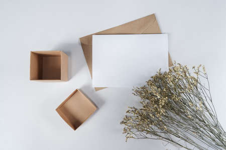 Blank white paper on brown paper envelope with Limonium dry flower and Carton box. Mock-up of horizontal blank greeting card. Top view of Craft paper envelope on white background. Flat lay minimalism Foto de archivo
