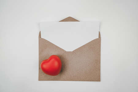 Blank white paper is placed on the open brown paper envelope with red heart. Horizontal blank greeting card on white background. Valentine's day concept Stock Photo