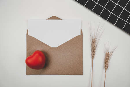 Blank white paper is placed on open brown paper envelope with red heart and Barley dry flower and black cloth on white background. Valentine's day concept