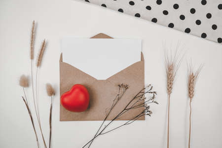 Blank white paper is placed on open brown paper envelope with red heart, Many kinds of dried flowers, white cloth on white background. Valentine's day concept Stock Photo