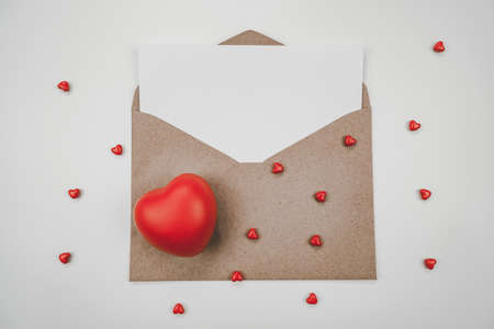 Blank white paper is placed on open brown paper envelope with red heart. Top view of Craft paper envelope on white background. Valentine's day concept