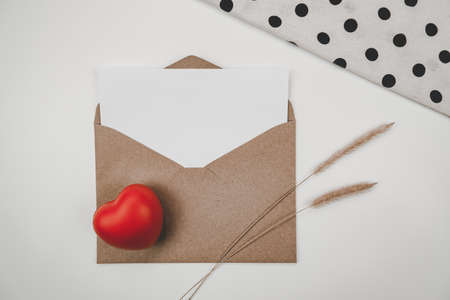 Blank white paper is placed on open brown paper envelope with red heart, Bristly foxtail dry flower, White cloth on white background. Valentine's day concept Stock Photo