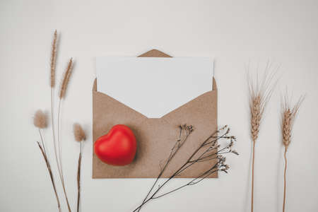 Blank white paper is placed on open brown paper envelope with red heart, Many kinds of dried flowers on white background. Valentine's day concept