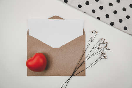 Blank white paper is placed on open brown paper envelope with red heart and Limonium dry flower and White cloth on white background. Valentine's day concept Stock Photo