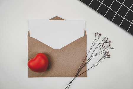 Blank white paper is placed on open brown paper envelope with red heart and Limonium dry flower and black cloth  on white background. Valentine's day concept