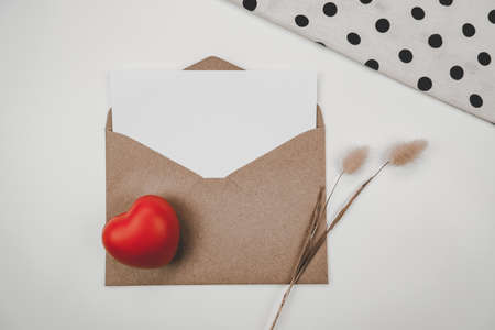 Blank white paper is placed on open brown paper envelope with red heart and Rabbit tail dry flower and White cloth on white background. Valentine's day concept