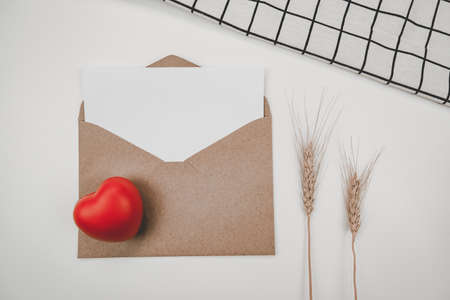 Blank white paper is placed on open brown paper envelope with red heart and Barley dry flower and White cloth on white background. Valentine's day concept Stock Photo
