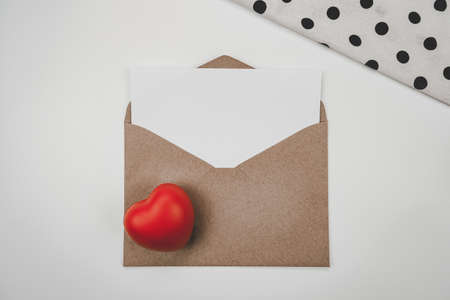 Blank white paper is placed on open brown paper envelope with red heart and White cloth  on white background. Valentine's day concept