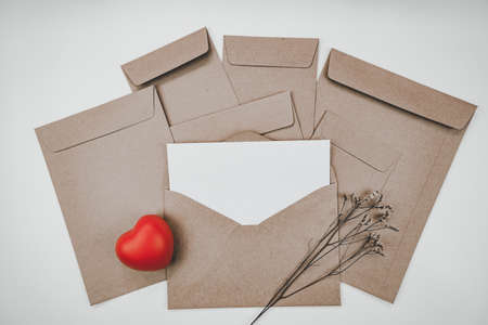 Blank white paper is placed on the open brown paper envelope with red heart and Limonium dry flower on white background. Valentine's day concept.