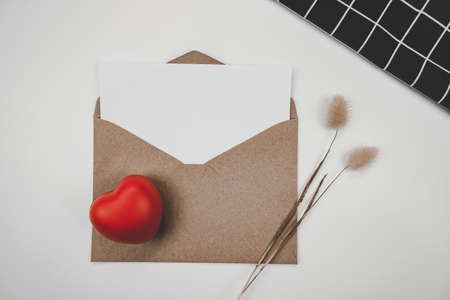 Blank white paper is placed on open brown paper envelope with red heart, Rabbit tail dry flower and black cloth  on white background. Valentine's day concept