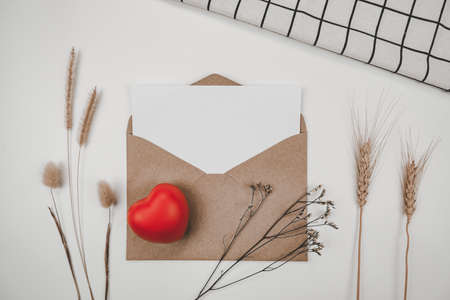 Blank white paper is placed on open brown paper envelope with red heart, Many kinds of dried flowers, White cloth on Black background. Valentine's day concept #valentine #card #gift #template #mockup Stock Photo