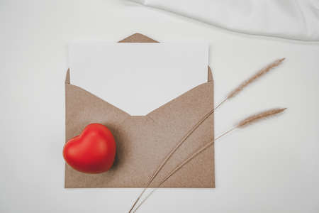 Blank white paper is placed on open brown paper envelope with red heart, bristly foxtail dry flower, White cloth on white background. Valentine's day concept