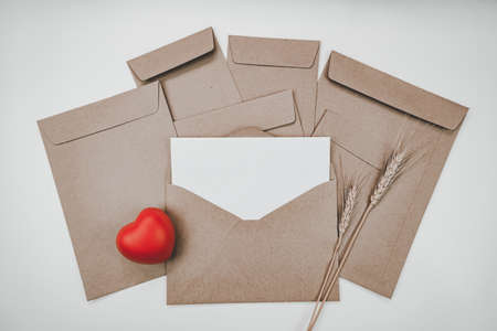 Blank white paper is placed on the open brown paper envelope with red heart and Barley dry flower on white background. Valentine's day concept. Stock Photo