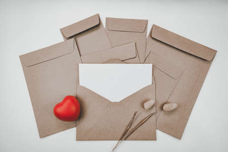 Blank white paper is placed on the open brown paper envelope with red heart and Rabbit tail dry flower on white background. Valentine's day concep