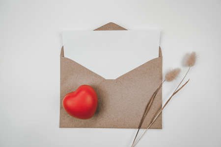 Blank white paper is placed on open brown paper envelope with red heart with Rabbit tail dry flower on white background. Valentine's day concept. Stock Photo