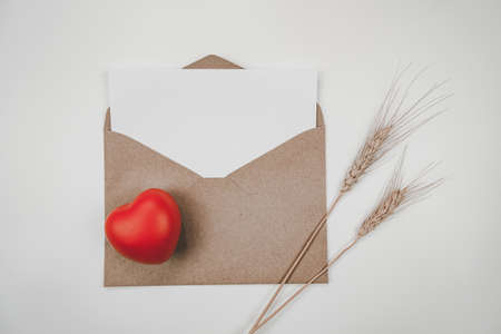 Blank white paper is placed on open brown paper envelope with red heart, Barley dry flower. Craft paper envelope on white background. Valentine's day concept. Stock Photo