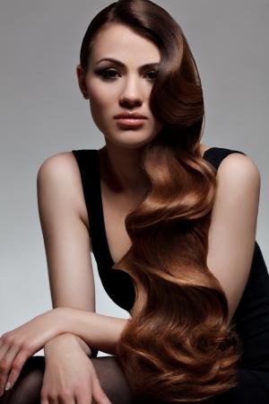 長いウェーブのかかった髪良い品質レタッチで美しい女性のブラウン髪の肖像画について