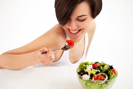 Diet. Beautiful young woman has breakefast. Bowl of salad