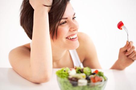 alimentos saludables: Retrato de la mujer feliz con plato de ensalada, contra el fondo blanco