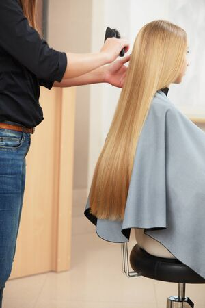 combing hair: Hairdresser combing woman with long blonde hair in salon