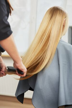 kapster: Kapper kammen lang blond haar in salon