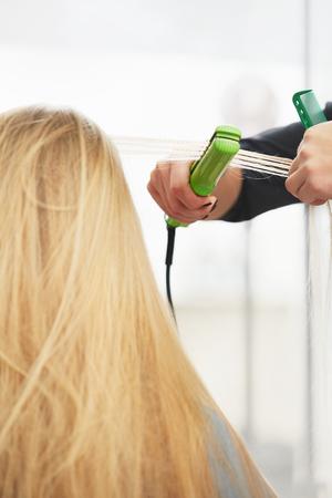 straightener: Hairdresser straighten hair with straightener