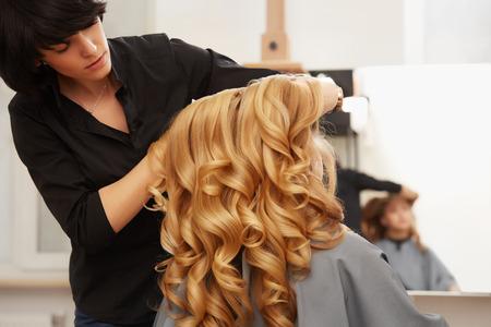 美容サロンでブロンドの巻き毛を持つ若い女性のためのヘアスタイルをやって