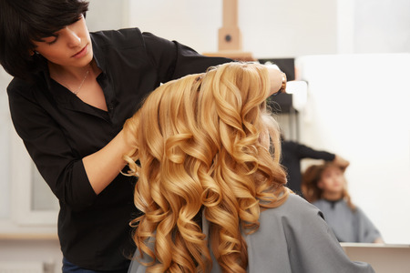 Hairdresser doing hairstyle for young woman with Blonde curly hair in salon