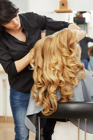 cabello rubio: Peluquero que hace el peinado para la mujer joven con el pelo rizado rubia en el sal�n