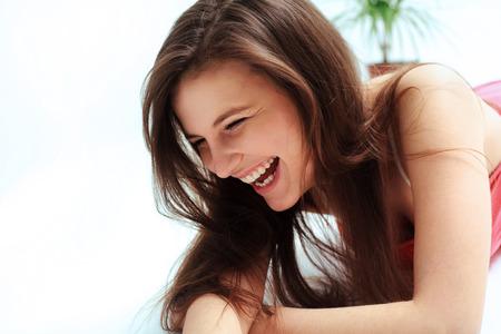lachendes gesicht: Glückliche Frau, die gegen weißen Hintergrund lachend